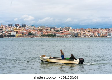 LISBON, PORTUGAL - NOVEMBER 04, 2018. Fisherman on their skiff on the river Tagus facing the city of Lisbon