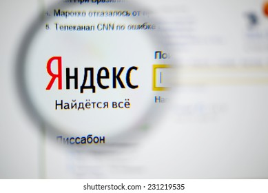 LISBON, PORTUGAL - NOVEMBER 17, 2014: Photo of Yandex homepage on a monitor screen through a magnifying glass.