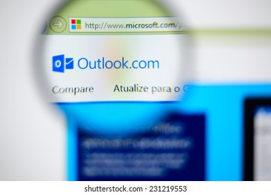 LISBON, PORTUGAL - NOVEMBER 17, 2014: Photo of Outlook homepage on a monitor screen through a magnifying glass.