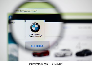 LISBON, PORTUGAL - NOVEMBER 17, 2014: Photo of BMW homepage on a monitor screen through a magnifying glass.