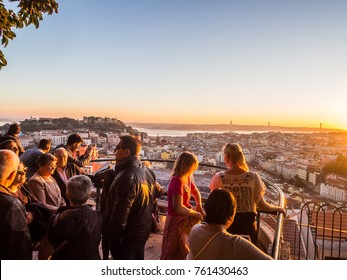 LISBON, PORTUGAL - NOVEMBER 19, 2017: Tourists at Belvedere of Our Lady of the Hill viewpoint, looking at the cityscape of Lisbon at sunset.