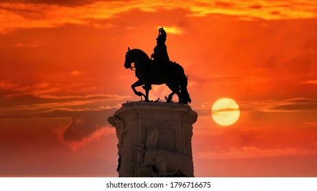 Lisbon, Portugal - November 2019: Silhouette of Equestrian statue of King John I in the Praca da Figueira square under dramatic red evening sun