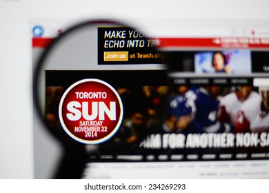 LISBON, PORTUGAL - NOVEMBER 30, 2014: Photo of the Toronto Sun homepage on a monitor screen through a magnifying glass.