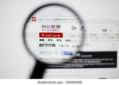 LISBON, PORTUGAL - NOVEMBER 30, 2014: Photo of Asahi Shimbun homepage on a monitor screen through a magnifying glass.