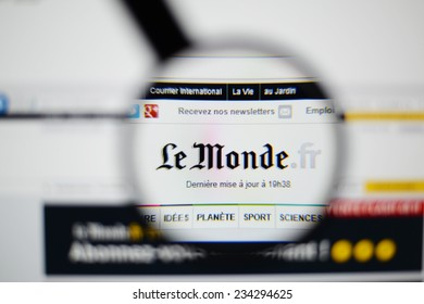 LISBON, PORTUGAL - NOVEMBER 30, 2014: Photo of Le Monde homepage on a monitor screen through a magnifying glass.
