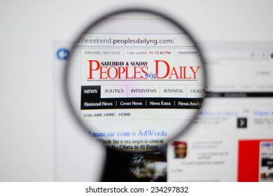 LISBON, PORTUGAL - NOVEMBER 30, 2014: Photo of The Peoples Daily homepage on a monitor screen through a magnifying glass.