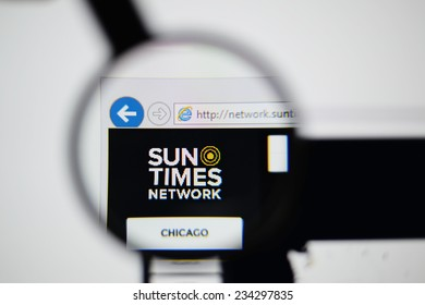LISBON, PORTUGAL - NOVEMBER 30, 2014: Photo of The Sun Times Network homepage on a monitor screen through a magnifying glass.