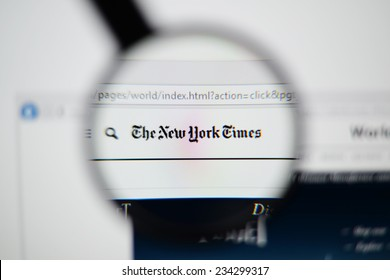 LISBON, PORTUGAL - NOVEMBER 30, 2014: Photo of The New York Times homepage on a monitor screen through a magnifying glass.