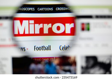 LISBON, PORTUGAL - NOVEMBER 30, 2014: Photo of the Mirror Online homepage on a monitor screen through a magnifying glass.