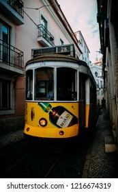 Lisbon, Portugal - Oct 24, 2018: Traditional yellow eletric tram in a narrow street in Alfama, Lisbon, Portugal