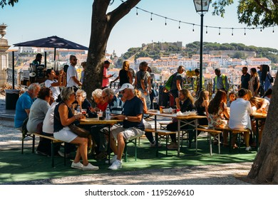 Lisbon, Portugal - Oct 3, 2018: Tourists enjoy drinks and food while overlooking the panoramic view over the center of Lisbon from the viewpoint called: Miradouro de Sao Pedro de Alcantara