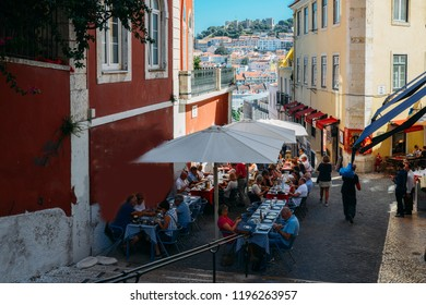 Lisbon, Portugal - Oct 3, 2018: Outdoor cafe on the old streets of Alfama, Lisbon overlooking Castelo Sao Jorge and Baixa
