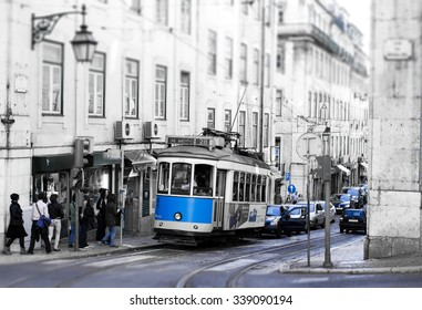 LISBON, PORTUGAL - OCTOBER 27, 2013 : Traditional vintage tram makes its way across central Lisbon streets stopping at the tram station. Black and white picture with blue elements.