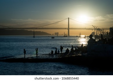 LISBON, Portugal- october 27, 2017: People watching the sunset with a view on 25 de Abril Bridge on Tejo River near Praca Do Comercio in Lisbon, Portugal.