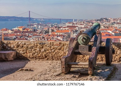 Lisbon, Portugal. Old bronze cannon in Sao Jorge aka Saint George Castle and a view of Lisbon Baixa District rooftops, the Tagus River and 25 de Abril Bridge