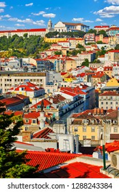 Lisbon Portugal. Panoramic top view at red tiled roofs of houses in antique historical district Alfama with cathedral on top of knoll. Sunny day with blue sky and clouds.