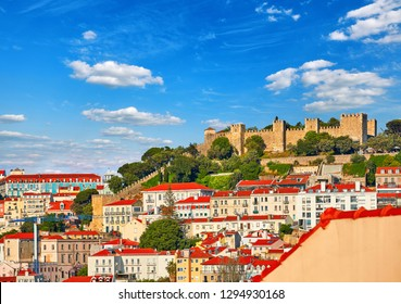 Lisbon, Portugal. Saint George Castle at knoll, antique district Alfama in downtown of Lisboa city. Ancient medieval stone walls above houses with red tegular roofs. Summer day with blue sky.
