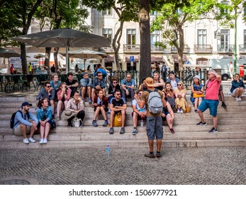 LISBON, PORTUGAL - SEPTEMBER 10, 2019: lots of tourists being lectured by a tourism guide in Lisbon, Portugal at the Cidade Alta neighborhood among its historic building on cobblestone   sidewalks.