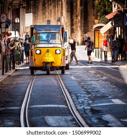 LISBON, PORTUGAL - SEPTEMBER 10, 2019: The historic architecture of Lisbon in Portugal showcasing its cobblestone streets being used by a traditional Portuguese Tuk Tuk tourism car.