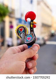 LISBON, PORTUGAL - SEPTEMBER 10, 2019: One of the most famous icon of Portugal, the colorful hand painted porcelain rooster with the historic buildings of Lisbon on the background.