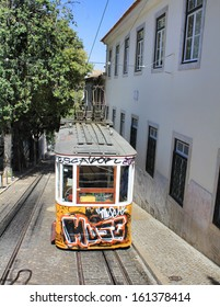 LISBON, PORTUGAL - SEPTEMBER 10: Yellow tram covered with graffiti on September 10, 2013 in Lisbon Portugal. Yellow tram (funicular) is the symbol and the tourist attraction of Lisbon.