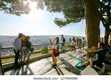LISBON, PORTUGAL - SEPTEMBER 10th, 2018 : Tourists enjoying the view from one of the gorgeous viewpoints of Graca district in Lisbon, Portugal. They're taking group pictures and listening to music.