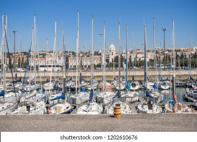 Lisbon, Portugal, September 11, 2018: View The Jerónimos Monastery or Hieronymites Monastery near the Tagus river in the parish of Belém throuh local harbor and sailing boats masts under blue sky