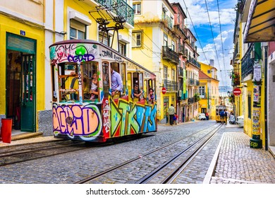 LISBON, PORTUGAL - SEPTEMBER 12, 2014: Pedestrians and trams in Lisbon. The historic trams are a popular attraction.