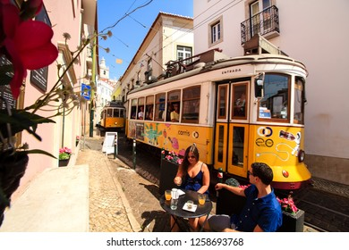 LISBON, PORTUGAL - SEPTEMBER 14th, 2018 : young couple taking breakfast at the open cafe terrace with famous vintage yellow trams running just besides their table on the narrow street of the downtown