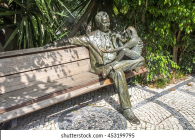 Lisbon, Portugal - September 20, 2014:  Sculpture of man and monkey sitting on a bench at Lisbon zoo.
