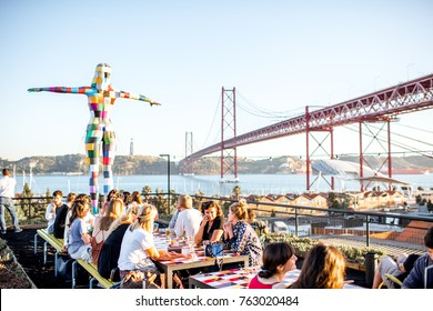 LISBON, PORTUGAL - September 27, 2017: View on the 25th of April bridge with people sitting on the bar terrace during the sunset in Lisbon city, Portugal