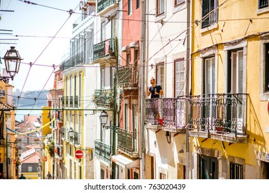LISBON, PORTUGAL - September 28, 2017: Street view with beautiful old buildings and man on the balcony in Lisbon during the sunny day in Portugal