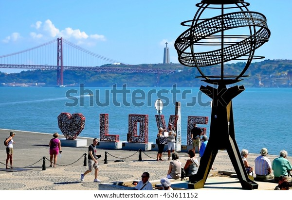 LISBON, PORTUGAL - SEPTEMBER 30, 2015: People on the River Tagus embankment with the 25th of April bridge and the Jesus Christ monument in the background, Lisbon, Portugal