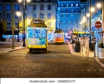 LISBON, PORTUGAL - SEPTEMBER 8, 2019: The architecture of Lisbon in Portugal at night with its famous trams, historic building, tiles, and cobblestone street and sidewalks.