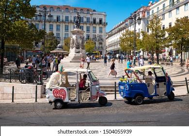 LISBON, PORTUGAL, SEPTEMBER 8, 2019: The historic architecture of Lisbon in Portugal showcasing its buildings, cobblestone streets, tiles, tuk tuk cars, and famous designed sidewalks on a sunny mornin