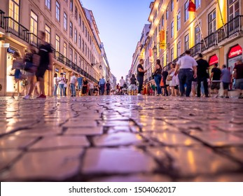 LISBON, PORTUGAL - SEPTEMBER 8, 2019: The historic architecture of Lisbon in Portugal at night, showcasing its famous cobblestone sidewalks and ancient buildings converted to stores.
