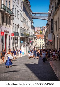 LISBON, PORTUGAL - SEPTEMBER 8, 2019: The historic city of Lisbon in Portugal showcasing the Cidade Alta neighborhood with its stores, cobblestone street, designed sidewalks, and tons of locals and t