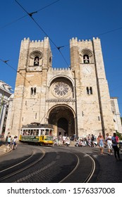 Lisbon, Portugal - September 8, 2019: Traditional tram and tourists in front of the Lisbon Cathedral (Patriarchal Cathedral of St. Mary Major), also known as Se, in Lisbon, Portugal, on a sunny day.