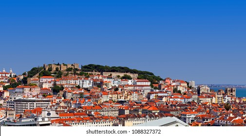 Lisbon, Portugal. View of the Castelo de Sao Jorge Castle aka Saint or St. George Castle, the Baixa, Alfama and Mouraria Districts. Typical Portuguese orange rooftops.