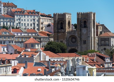 LISBON, PORTUGAL-AUGUST 14, 2019: Lisbon cathedral (Sé de Lisboa) among typical white houses with tiled orange roofs on hill. The Roman Catholic cathedral
