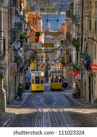 LISBON, PORTUGAL-JUNE 10: Two trams 28 passing each other in famous Bica funicular, near Bairro Alto, rich decorated street with portugese flags in Lisbon, capital of Portugal, June 10, 2008, Lisbon