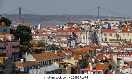 Lisbon red tiled rooftops with the bridge creating a line on the horizon