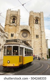 Lisbon street with the typical yellow tram and Lisbon Cathedral on the background.