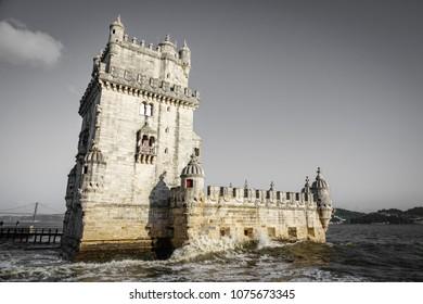 Lisbon Torre de Belem with waves breaking against gray sky