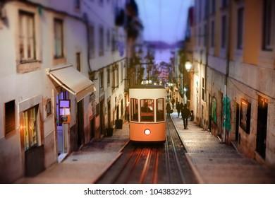 Lisbon yellow tram funicular in old city, Portugal. Tilt-shift effect