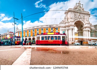 Lisbon,Portugal. Colorful street photography. Tourism in the historic tram of the city.Triumphal Arch in Commerce Square at sunset with sun and clouds.