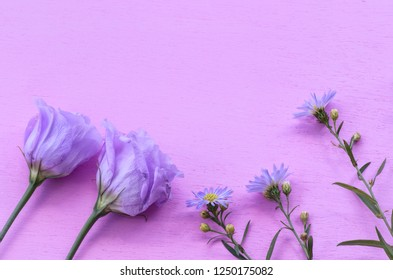 Lisianthus and Asters with copy space, on a pink wooden background.