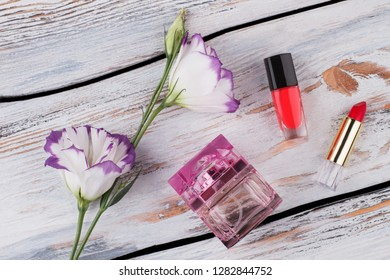 Lisianthus flowers and makeup accessories. Flat lay. White wood background.