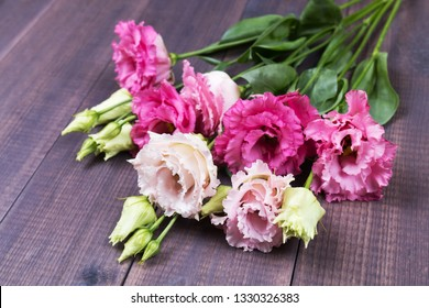 Lisianthus. White and rose eustoma bouquet on a wooden background. Angle view