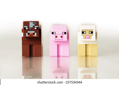 Liskeard, United Kingdom, March 1 2015. A studio shot of the Lego Minecraft cow, pig and sheep figures. Lego is extremely popular with child and adult collectors worldwide.
